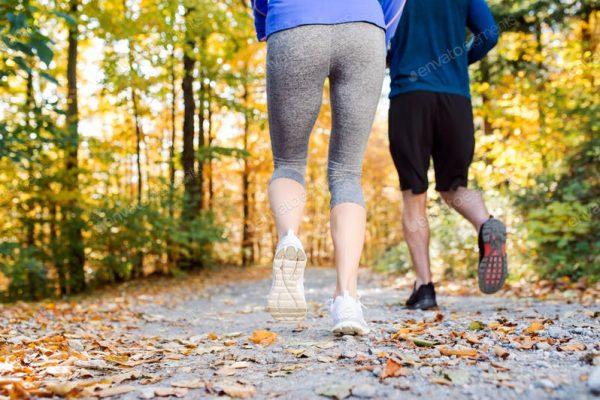 Mann und Frau machen Sport im Wald bei Sonnenschein trotz Thrombose