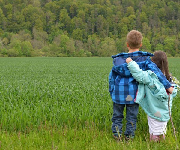 Kinder spazieren im Gras und tragen lange Kleinung, um sich vor Zecken zu schützen