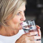 Alte Frau beugt Ihren Kopfschmerzen vor und trinkt viel Flüssigkeit in Form von Wasser